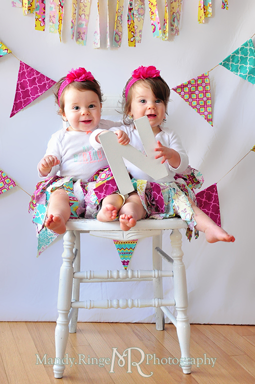 Twin girl's first birthday portraits // White chair, fabric pennants, rag banner, rag skirt, pink, teal, fuchsia, yellow, holding letters to spell ONE // by Mandy Ringe Photography