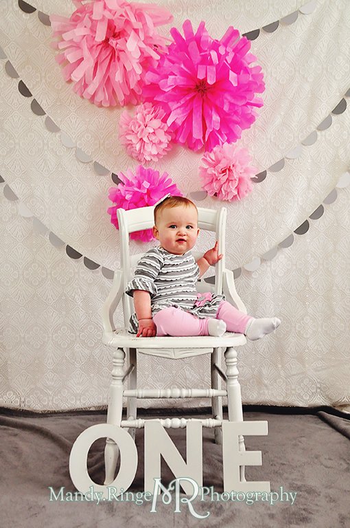 Baby girl's first birthday photo shoot. Sitting on a white chair with letters spelling out ONE. Pink tissue paper poms, gray paint chip garland // Pink, gray and white birthday // by Mandy Ringe Photography