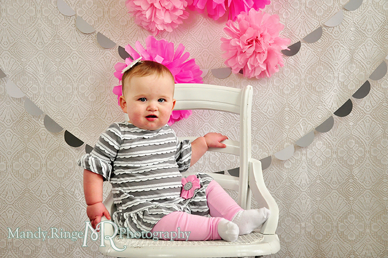 Baby girl's first birthday photo shoot. Pink tissue paper poms, gray paint chip garland // Pink, gray and white birthday // by Mandy Ringe Photography