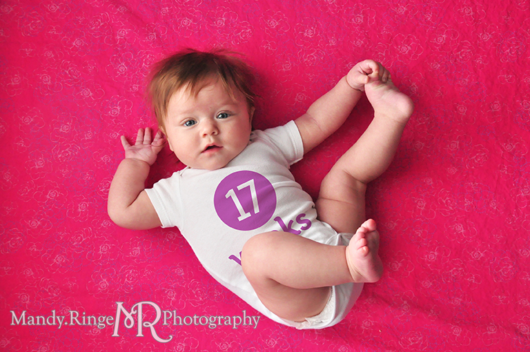 Weekly photos of a baby girl for the first year // Laying on a fabric backdrop, photoshopped numbers on white onesies // by Mandy Ringe Photography