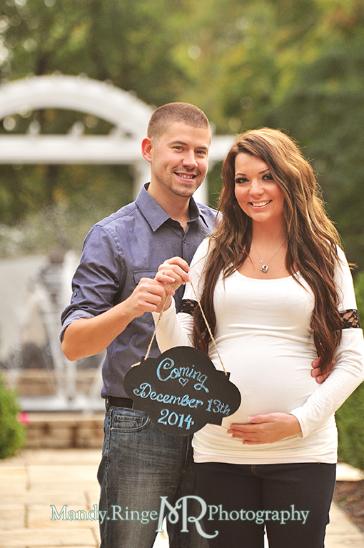 Man and pregnant woman posing in front of a white arch and fountain holding a chalkboard sign announcing the due date // Maternity portraits // Hurley Gardens - Wheaton, IL // by Mandy Ringe Photography