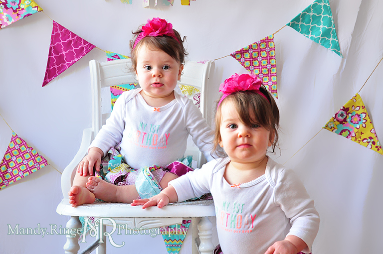 Twin girl's first birthday portraits // White chair, fabric pennants, rag banner, rag skirt, pink, teal, fuchsia, yellow, tissue paper pom poms // by Mandy Ringe Photography