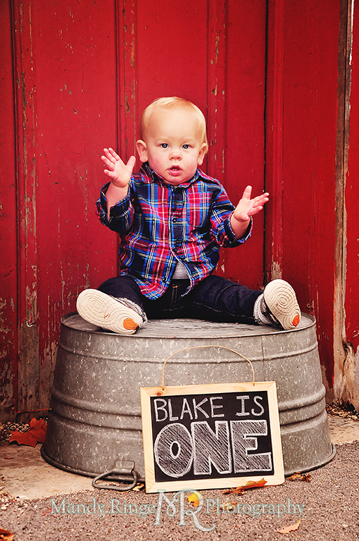 1 year old boy sitting on a wash tub in front of a red barn with chalkboard // First birthday portraits // Leroy Oaks - St Charles, IL // by Mandy Ringe Photography