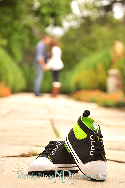 Baby shoes in focus in the foreground with man and woman blurred and kissing in the background // Maternity portraits // Hurley Gardens - Wheaton, IL // by Mandy Ringe Photography