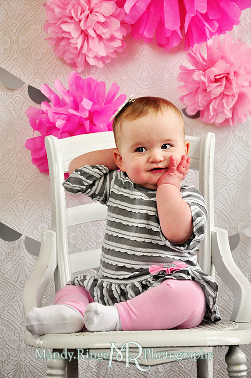 Baby girl's first birthday photo shoot. Sitting on a white chair. Pink tissue paper poms, gray paint chip garland // Pink, gray and white birthday // by Mandy Ringe Photography