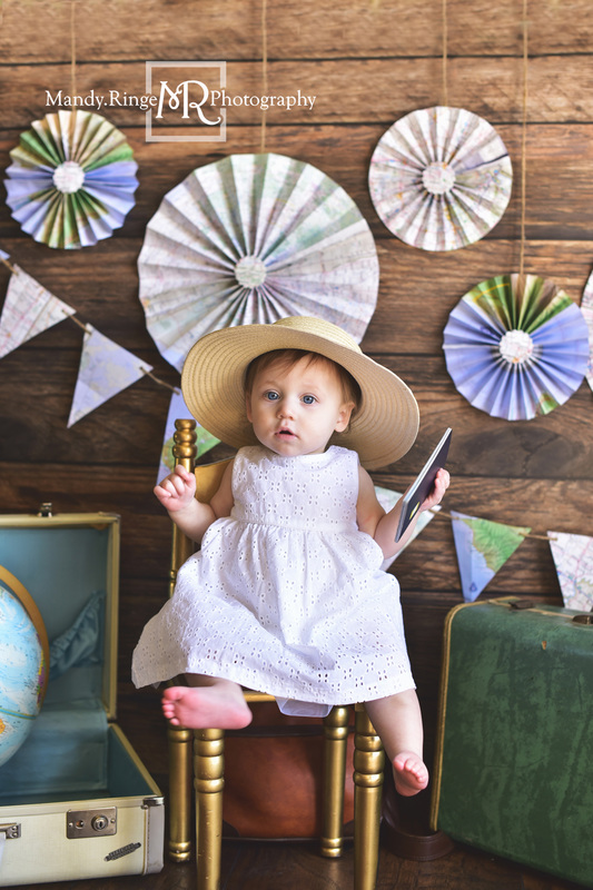 Little Traveler first birthday portraits // World traveler, maps, globe, suitcases, pennant banner, paper fans, little girl, passport // Traveling studio - client's home, Batavia, IL // by Mandy Ringe Photography