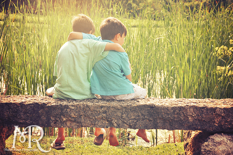 Brothers embracing on a stone bench overlooking a pond // Leroy Oaks // by Mandy Ringe Photography