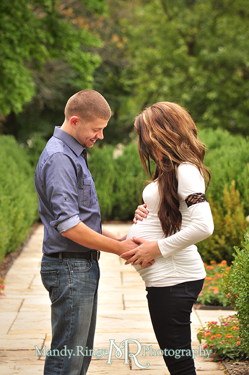 Man and pregnant woman facing each other with the man holding her belly // Maternity portraits // Hurley Gardens - Wheaton, IL // by Mandy Ringe Photography