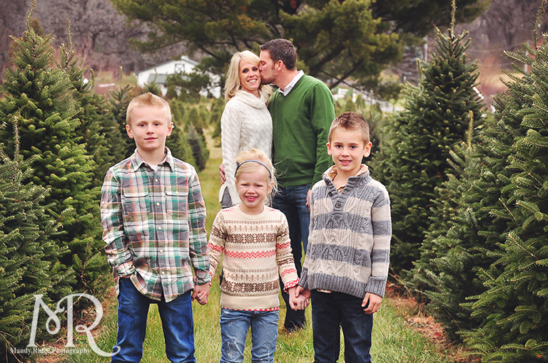 Family Christmas Portrait // Christmas Tree Farm // standing in between rows of trees with the kids in front and the parents in back kissing // by Mandy Ringe Photography