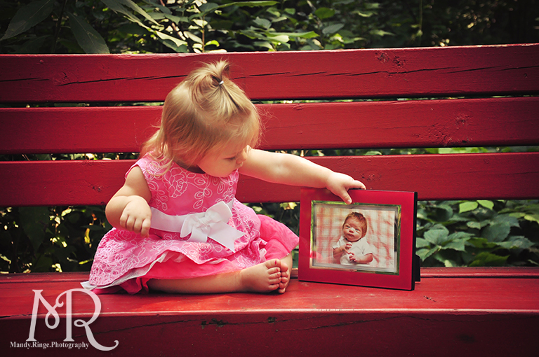 First birthday photos. Baby girl sitting with her newborn photo. // Delnor Woods Park // by Mandy Ringe Photography