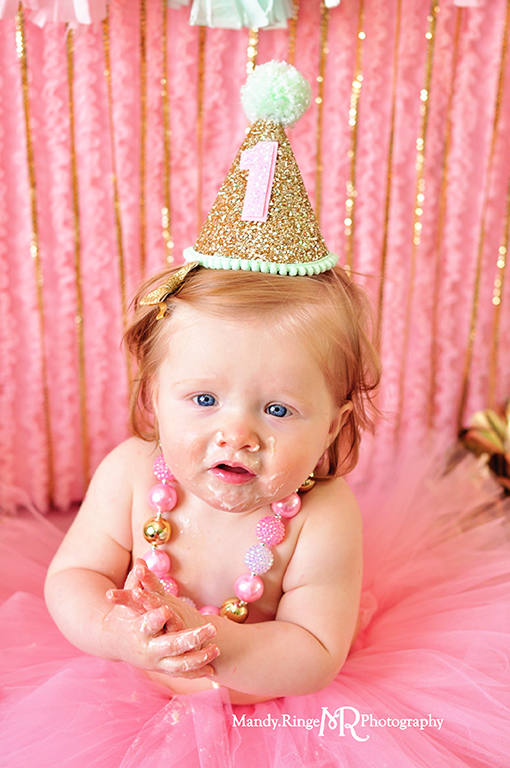 Pink, gold, and mint first birthday // Smash cake session // Tassle garland, tissue poms, pink ruffle fabric backdrop, gold sequin strands // St Charles, IL // by Mandy Ringe Photography