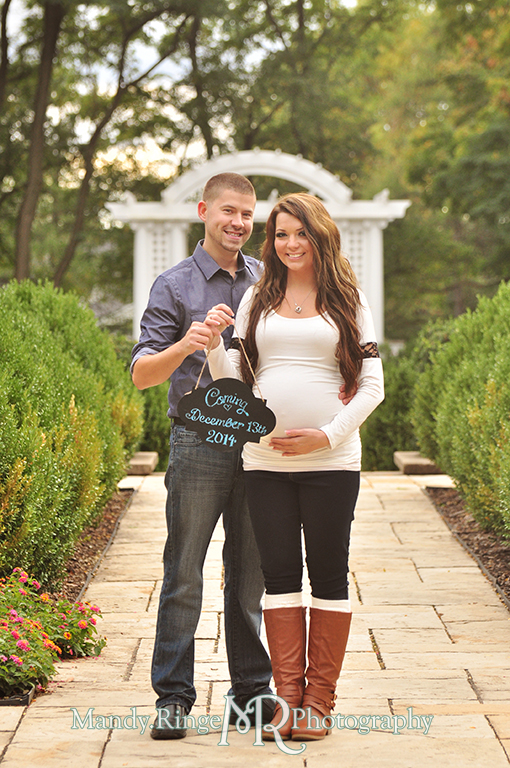 Man and pregnant woman posing in front of a white arch holding a chalkboard sign announcing the due date // Maternity portraits // Hurley Gardens - Wheaton, IL // by Mandy Ringe Photography