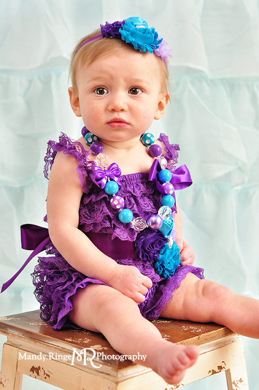 Baby girl's first birthday portraits // Purple, teal and aqua // Aqua ruffle backdrop, purple ruffle romper, fabric flower headband, chunky necklace // by Mandy Ringe Photography
