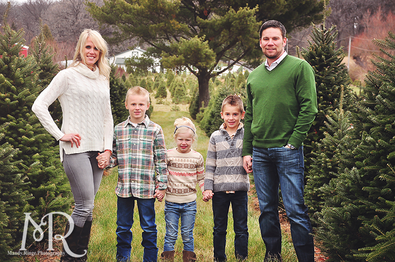 Family Christmas Portrait // Christmas Tree Farm // simple Christmas photo idea, standing in a row between pine trees // by Mandy Ringe Photography
