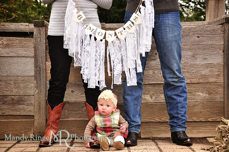 6 month old baby girl portraits // Baby sitting on the ground by parents feet with parents holding a lace rag garland and a banner that says 6 months // Cantigny Gardens - Wheaton, IL // by Mandy Ringe Photography