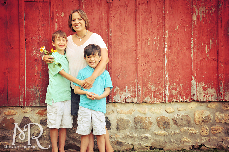 Family of three standing in front of a red barn // Leroy Oaks // by Mandy Ringe Photography