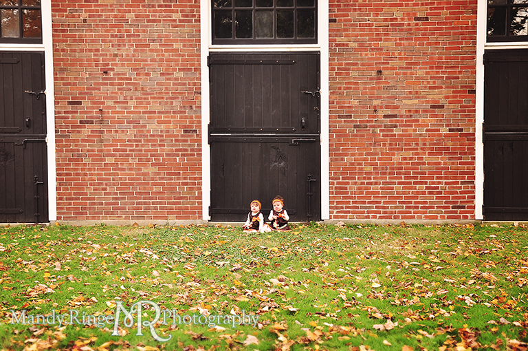 Fall portraits of 9 month old twins wearing Thanksgiving dresses // Sitting in front of brick stables // St. James Farm - Wheaton, IL // by Mandy Ringe Photography